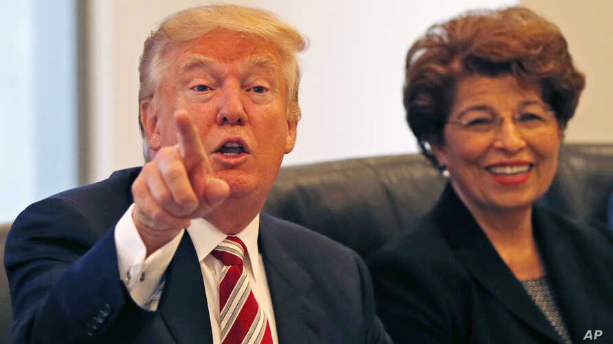 Republican presidential candidate Donald Trump holds a Hispanic advisory roundtable meeting in New York, Aug. 20, 2016. At right is Jovita Carranza, former Small Business Administration Deputy Administrator.