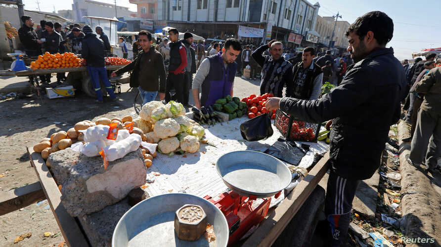 People do shopping after returning to their homes in the Al-Zuhoor neighborhood of Mosul, Iraq, Jan. 12, 2017.