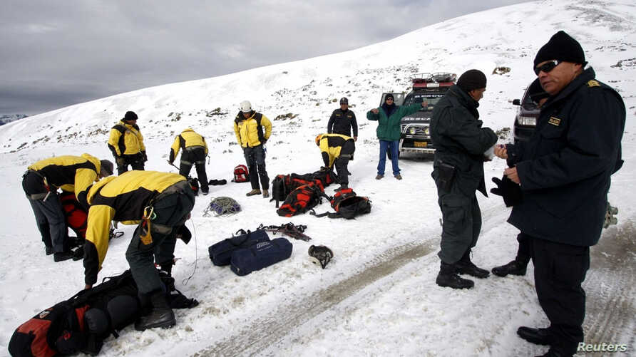 Police officers take part in a search and rescue operation for a helicopter that has disappeared with 14 people aboard in the Hualla Hualla area of the Quispicanchis province in Cuzco, Peru, June 8, 2012.