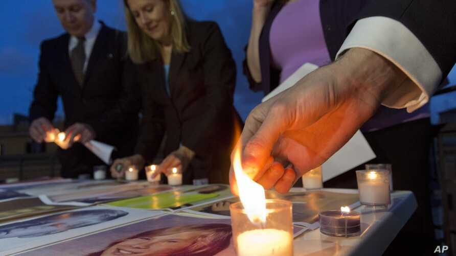 FILE - Members of Survivors Network of those Abused by Priests (SNAP) light candles during a protest to denounce abuses in Rome, April 25, 2014.
