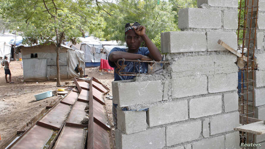 FILE - Haitian woman Romaine, one of the thousands made homeless by the 2010 earthquake, leans on a wall being built by the owners of the land where she lives in Shelter Camp 3, one of 385 informal 'tent cities' still existing since the disaster, in