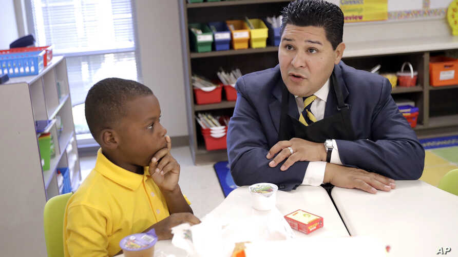 Houston Independent School District Superintendent Richard Carranza, right, talks with second grader John Bradford, 7, after handing out breakfast to students on their first day of school at Codwell Elementary School, Sept. 11, 2017, in Houston.