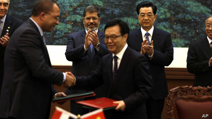 Egyptian President Mohammed Morsi, center left, and Chinese President Hu Jintao, center right, applaud as officials from both countries exchange documents during a signing ceremony at the Great Hall of the People in Beijing, China, August 28, 2012.