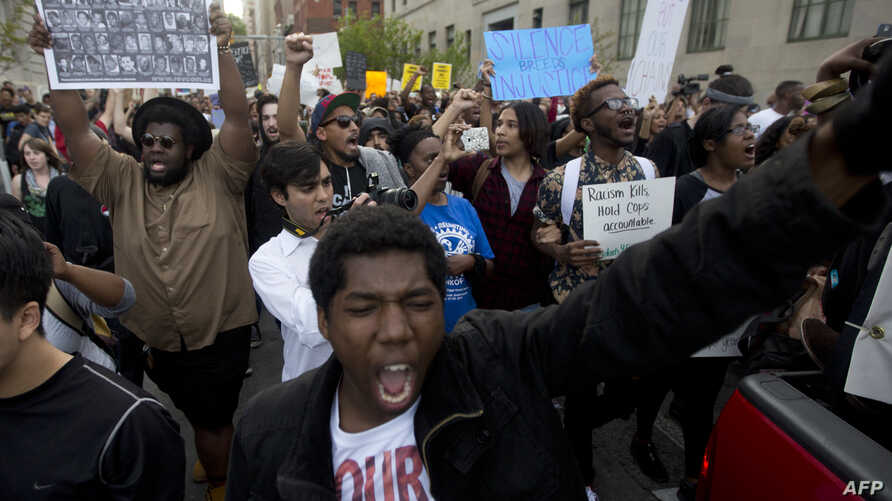 A demonstrator shouts during a protest in downtown Baltimore, Maryland, on April 29, 2015, seeking justice for an African-American man who died of severe spinal injuries sustained in police custody.