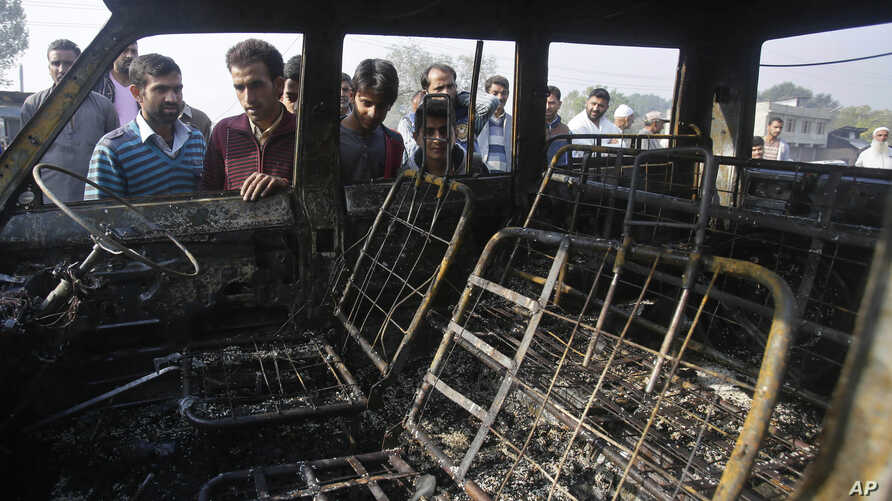 FILE - People look at the burned remains of a passenger vehicle on the outskirts of Srinagar in Indian-controlled Kashmir, Oct. 17, 2016. Kashmir is witnessing the largest protests against Indian rule in recent years, sparked by the July 8 killing of