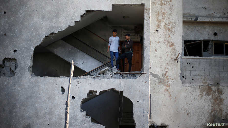 Palestinians look out of their house that was damaged in an Israeli air strike, in Gaza City, Nov. 13, 2018.