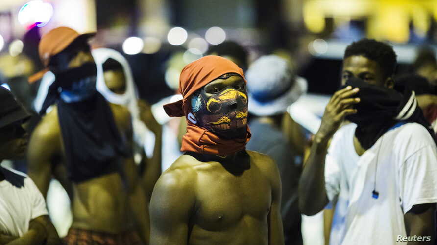 Young men wait to see to see what happens during another night of demonstrating in Ferguson, Missouri, August 12, 2015.