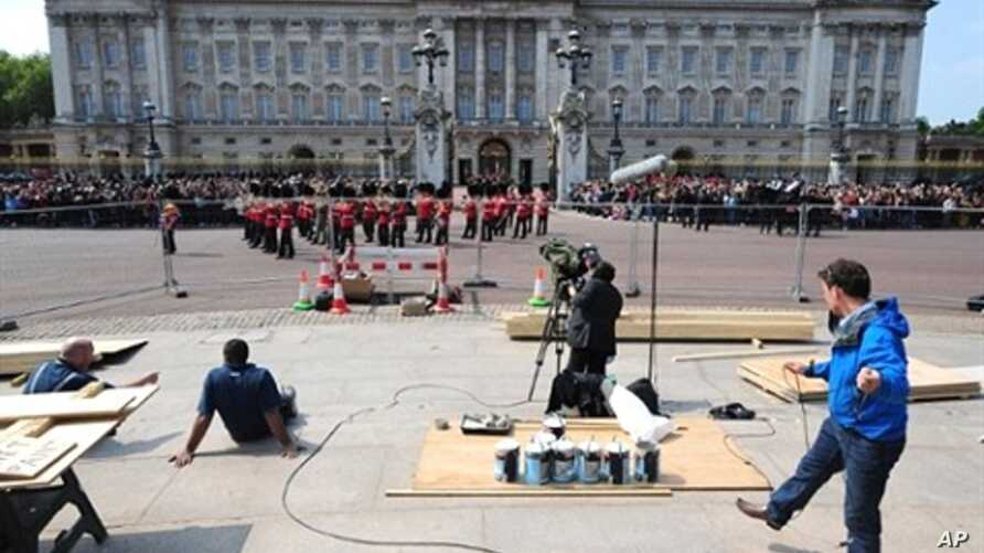 A TV crew works as members of the household brigade marching band walk in front of Buckingham palace, in London, on April 28, 2011.