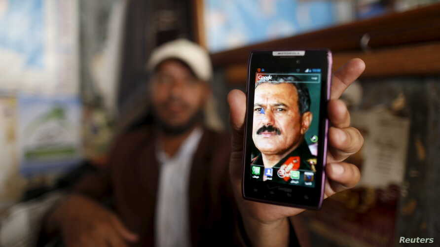 FILE - A man displays a picture of Yemen's former president, Ali Abdullah Saleh, on his mobile phone as he sits at a barber shop in the old quarter of Sana'a, Yemen June 16, 2015.