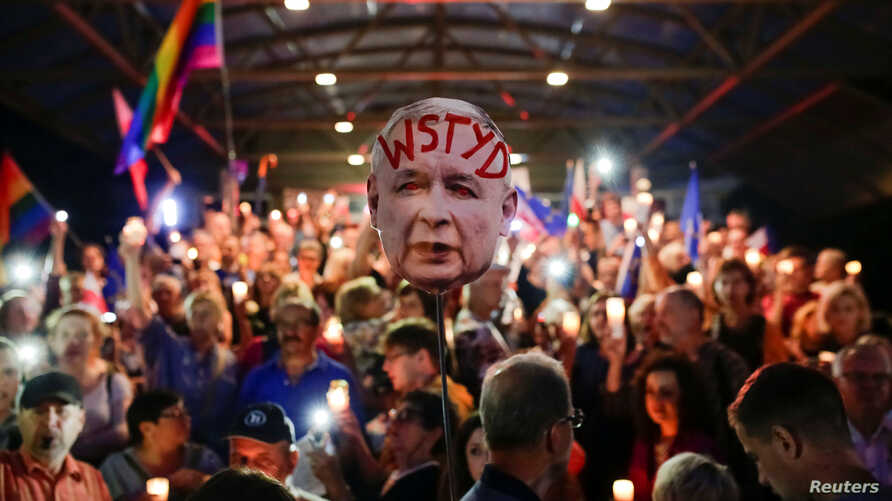 """People hold a sign that reads """"Shame,"""" depicting Law and Justice (PiS) party leader Jaroslaw Kaczynski, as they gather during the protest against judicial overhaul in Cracow, Poland, July 26, 2018."""