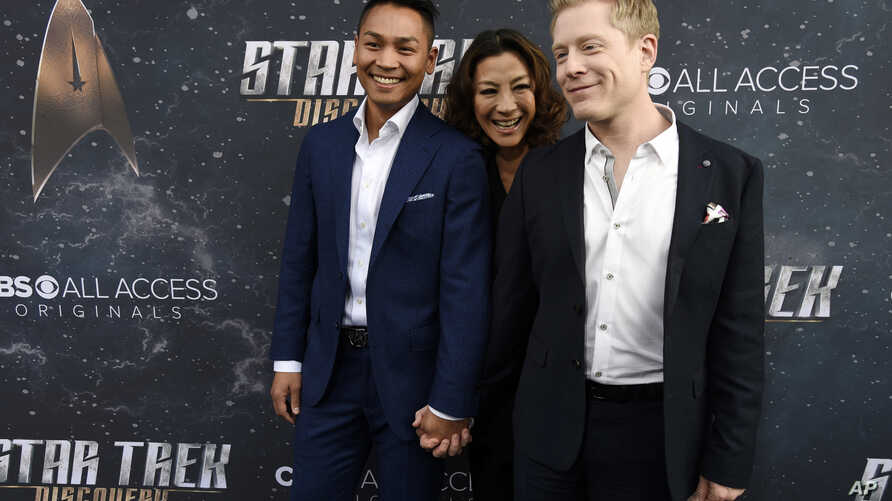 """FILE - Anthony Rapp (R), a cast member in """"Star Trek: Discovery,"""" poses with his boyfriend Teerakeni and fellow cast member Michelle Yeoh at the premiere of the new television series in Los Angeles, Sept. 19, 2017."""