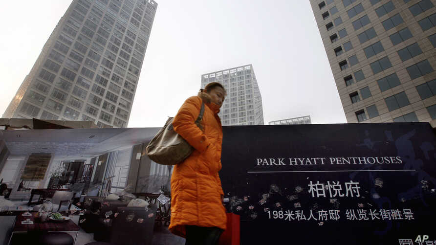 FILE - A Chinese woman walks past a property advertisement on display against residential buildings in Beijing.