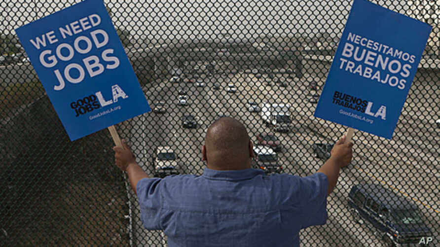 """South Los Angeles resident Christian Del Cid waves banners calling for good jobs, on a bridge in front of oncoming traffic at the Interstate I-110 overpass on a """"structurally deficient"""" bridge to call on U.S. Congress to provide funding for highway i"""