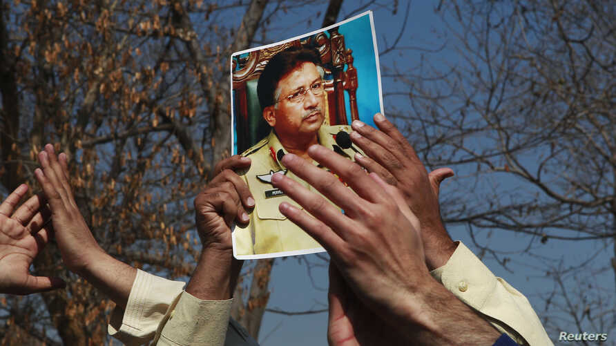 A supporter holds a picture of former Pakistani President Pervez Musharraf, during a protest with others at the Special Court where Musharraf will attend his trial in Islamabad, Feb. 18, 2014.
