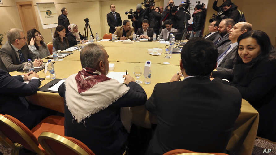 The Yemeni Houthi rebel delegation, background, and delegates of the internationally recognized Yemeni government, foreground, meet for a second day for talks on implementing a prisoner exchange agreed to in Sweden last month, in Amman, Jordan, Thurs