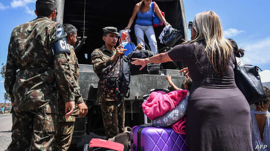 Venezuelans get off a Brazilian army truck after being given a ride by Brazilian soldiers while crossing the Brazilian-Venezuelan border, into Pacaraima, Roraima state, Brazil, Feb. 27, 2019.