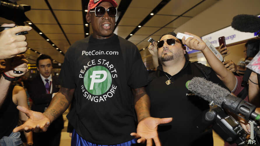 Former NBA basketball player Dennis Rodman, and Chris Volo, right, arrive at Singapore's Changi Airport, June 12, 2018.