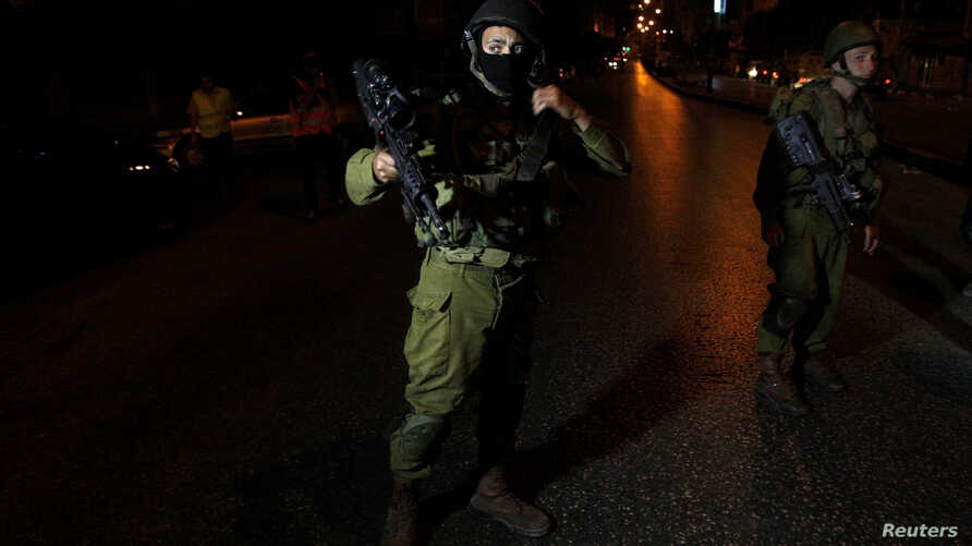 Israeli soldiers take part in an operation to locate three Israeli teens in the West Bank City of Hebron, June 20, 2014.