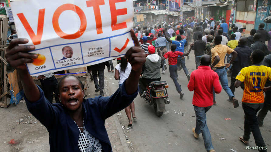 A supporter of Kenyan opposition leader Raila Odinga carries a banner and shouts slogans as others run along a street in Humura neighbourhood, in Nairobi, Kenya August 10, 2017.