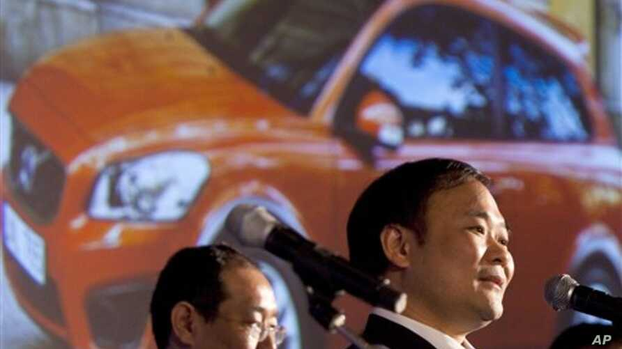 Li Shufu, right, chairman of Chinese automaker Geely, speaks while a photo of a Volvo car is projected on a screen during a press conference in Beijing, 30 Mar 2010