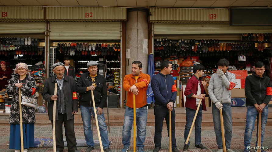 Shopkeepers line up with wooden clubs to perform their daily anti-terror drill outside the bazaar in Kashgar, Xinjiang Uighur Autonomous Region, China, March 24, 2017.