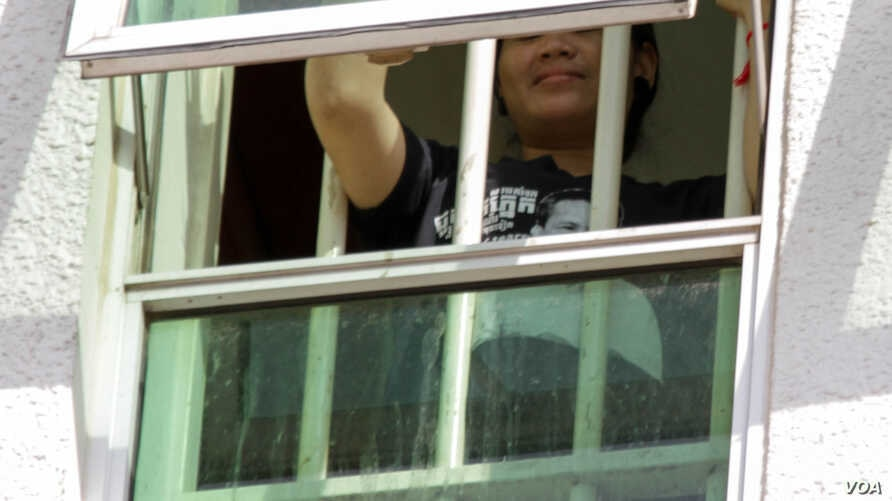 Tep Vanny waves her hands from a window at Phnom Penh Municipal Court as she is questioned by the court over his Black Monday campaign,  on Wednesday, August 17, 2016 in Phnom Penh. ( Leng Len/VOA Khmer) ​​​​