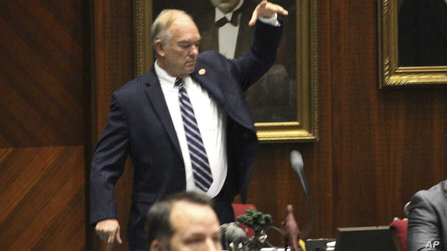 Arizona Republican state Rep. Don Shooter drops his mic after voting no on a resolution expelling him from the Arizona House for a pattern of sexual harassment in Phoenix, Arizona, Feb. 1, 2018.