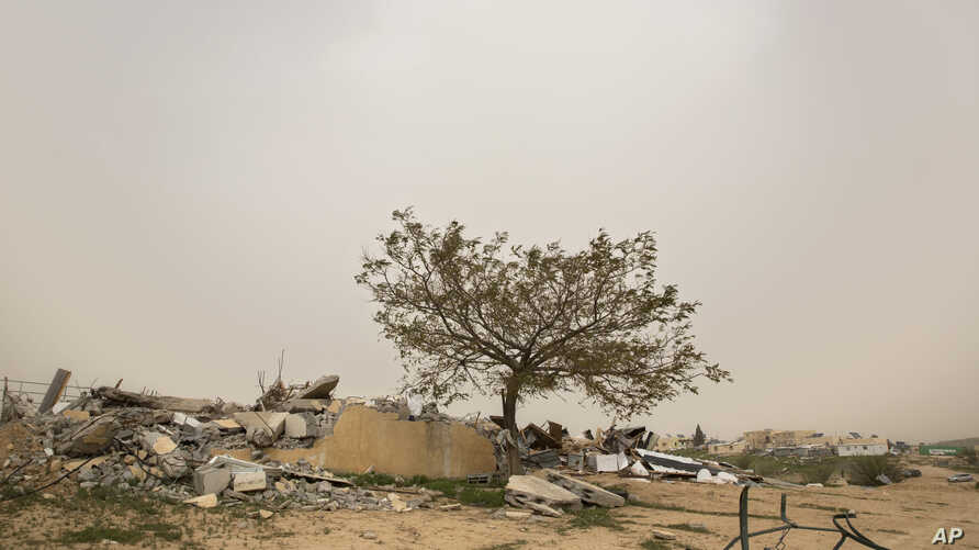 A tree stands near debris from demolished homes, in the Bedouin village of Umm al-Hiran, Israel, March 12, 2017.