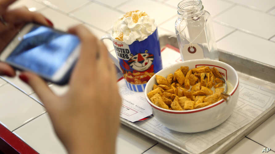 A woman takes a picture of her breakfast at Kellogg's Cafe NYC in New York, Dec. 14, 2017.