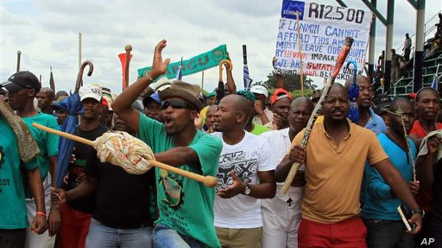 Mine workers sing and dance outside the Lonmin's platinum mine in Marikana near Rustenburg, South Africa, Thursday, Jan. 30, 2014. The Association of Mineworkers and Construction Union (Amcu) on Thursday rejected a 9% wage offer from leading platinum