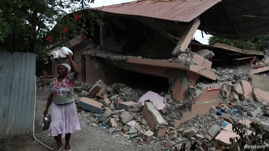 A woman walks past a school, which was damaged in an earthquake that hit northern Haiti late on Saturday, in Gros Morne, Haiti, Oct. 8, 2018.