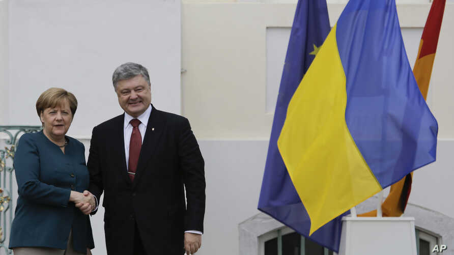 FILE - German Chancellor Angela Merkel, left, welcomes the President of Ukraine Petro Poroshenko at the government guest house Meseberg Palace in the village of Meseberg about 70 kilometers ( 44 miles) north of in Berlin, May 20, 2017.