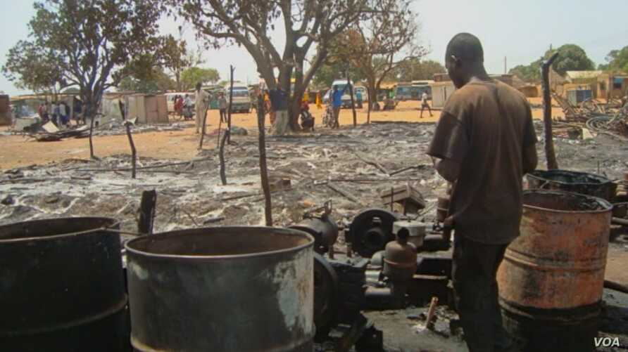 A man looks over what remains of one of the dozens of shops that were gutted by fire in a market in Aweil, South Sudan on Thursday, March 28, 2013.