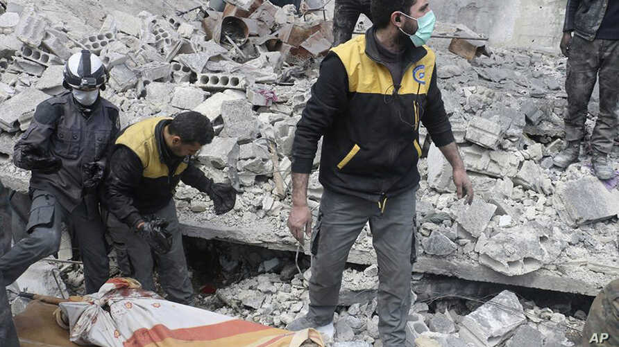 This photo released March 13, 2018, by the Syrian Civil Defense group known as the White Helmets, shows members of the White Hemets removing a body after airstrikes and shelling by Syrian government forces, in Ghouta.