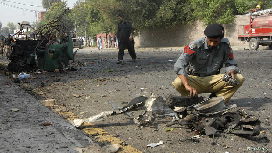 A police officer collects evidence from the site of a bomb attack on a Frontier Corps (FC) convoy in Peshawar, Sept. 23, 2014.