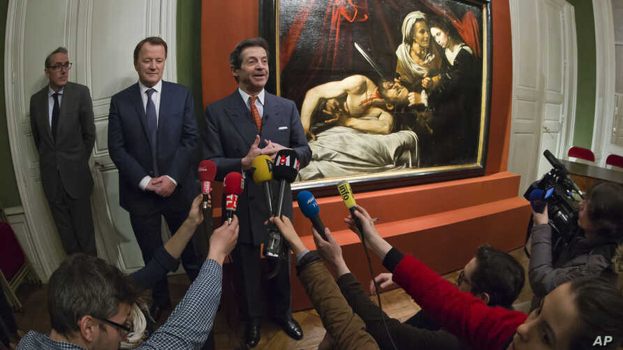 Auction officer Marc Labarbe, center left, and Eric Turquin expert specialized in old master paintings stand next to a 400-year-old painting that might have been executed by Italian master Caravaggio and could be worth more than 100 million euros,  f