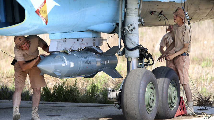 In this photo taken on Saturday, Oct.  3, 2015, Russian military support crew attach a satellite guided bomb to SU-34 jet fighter at Hmeimim airbase in Syria.