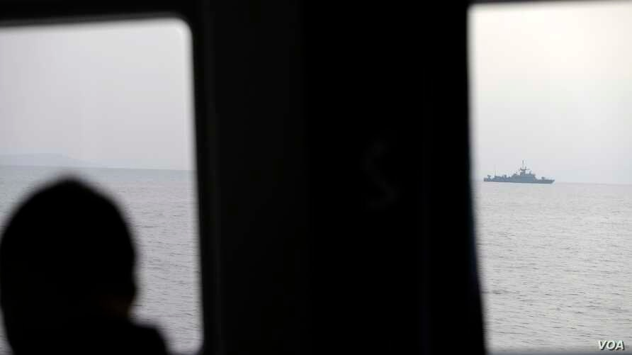 FILE - A Greek coast guard officer watches a NATO warship during a patrol on the Aegean Sea, March 17, 2017. A year later, a search and rescue operation is trying to locate about a dozen migrants whose boat reportedly sank.