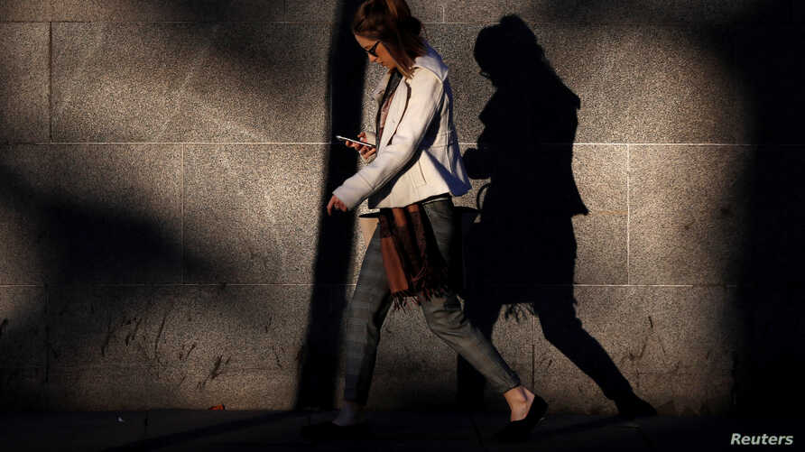 FILE - A young woman looks at her mobile phone early morning in Westminster, London, Britain, Oct. 10, 2016.