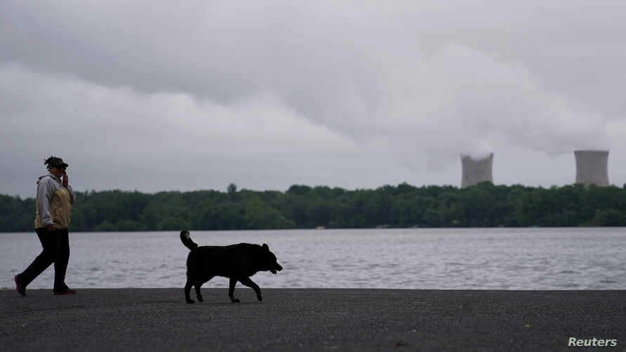 A woman walks her dog along the Susquehanna River in front of the Three Mile Island Nuclear power plant in Goldsboro, Pennsylvania, May 30, 2017.