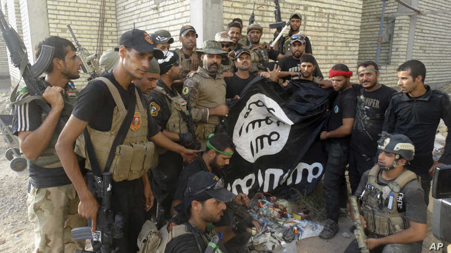 Iraqi security forces backed by Shiite and Sunni pro-government fighters celebrate as they hold a flag of the Islamic State militant group they captured in Anbar University in Ramadi, Anbar province, Iraq, July 26, 2015.