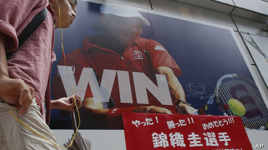 A man walks in front of a sporting goods store with a huge advertisement board showing Japan's tennis player Kei Nishikori, in Tokyo, Sunday, Sept. 7, 2014.