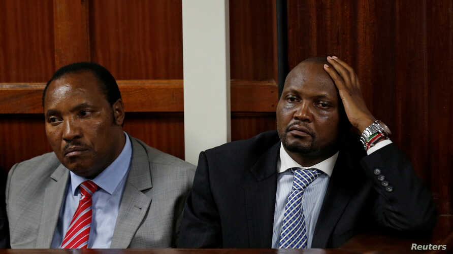 """FILE - Kenyan politicians Ferdinand Waititu and Moses Kuria sit in the dock at the Milimani Law Courts over alleged """"hate speech,"""" flagging growing tension in Kenya's capital Nairobi, June 14, 2016."""