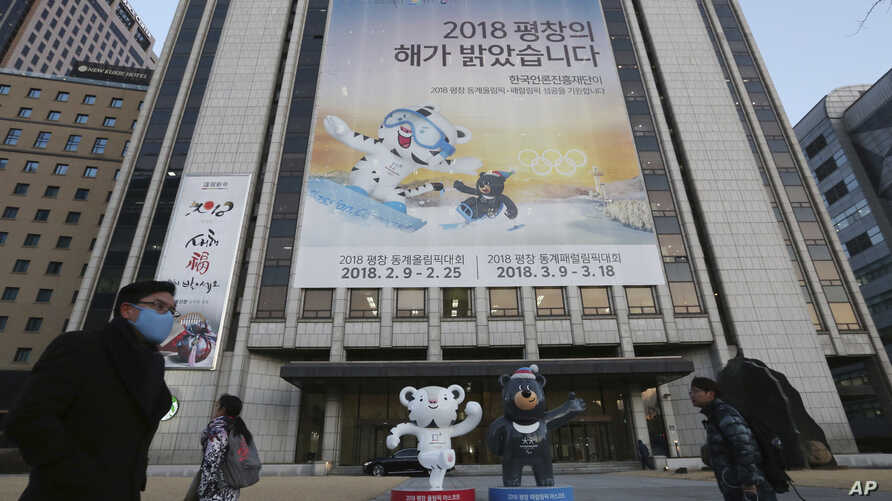 "People pass a banner promoting the upcoming 2018 Pyeongchang Winter Olympic as official mascots, a white tiger 'Soohorang' for the Olympic, and the Asiatic black bear ""Bandabi"" for the Paralympic (Bottom-R) are displayed in downtown in Seoul, South K"