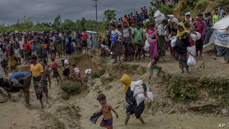 Rohingya Muslims, who crossed over from Myanmar into Bangladesh, walks through muddy field after collecting aid from a distribution centre near Balukhali refugee camp, Bangladesh, Thursday, Sept. 28, 2017.