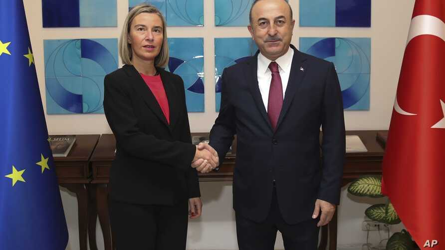 Turkish Foreign Minister Mevlut Cavusoglu, right, shakes hands with the European Union's foreign policy chief Federica Mogherini prior to their meeting, in Ankara, Turkey, Thursday, Nov. 22, 2018.