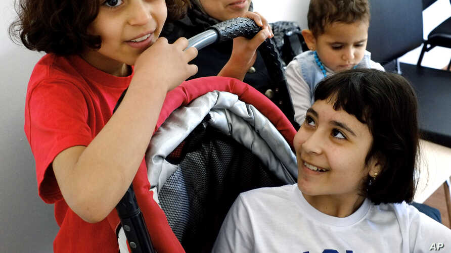 Amal Ismail eight year old, left, with her older sister Alaa, right, and their younger 18-month-old Aryam are seen by their mother Maha at the IOM 'International Organization for Migration' office in capital Nicosia, Cyprus. Fleeing the Syrian town