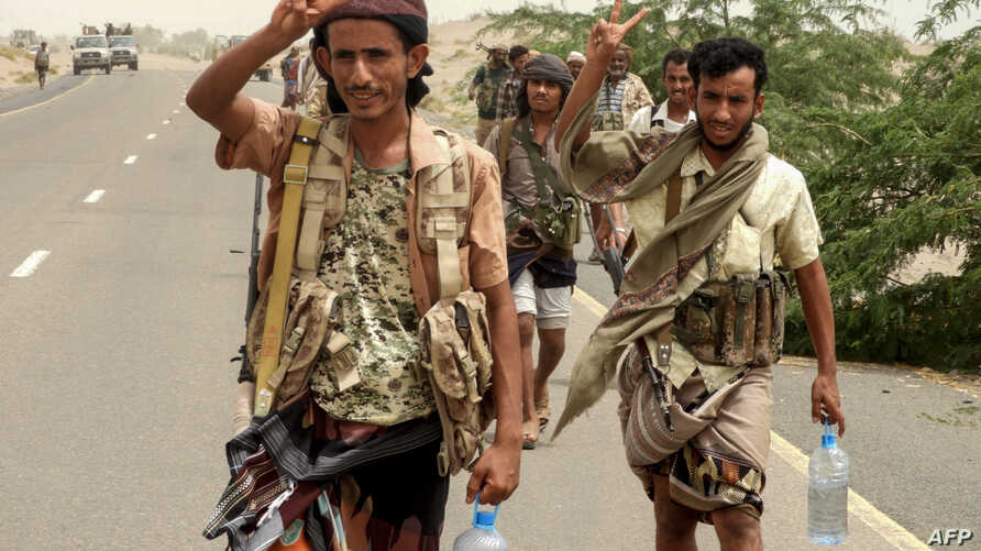 Yemeni pro-government forces flash the victory gesture as they arrive in al-Durayhimi district, about 9 kilometers south of Hodeidah international airport, June 13, 2018.