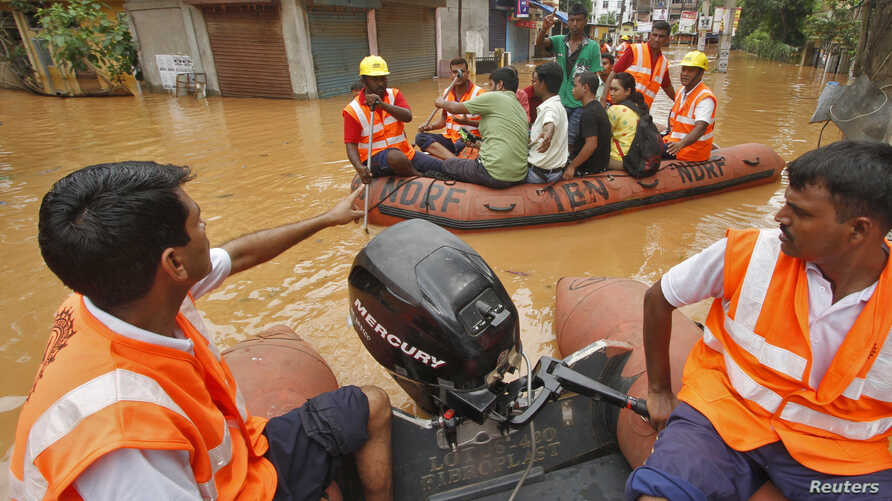 India's National Disaster Response Force (NDRF) personnel use rafts to rescue flood-affected residents after heavy rains at Guwahati in the northeastern Indian state of Assam, June 27, 2014.