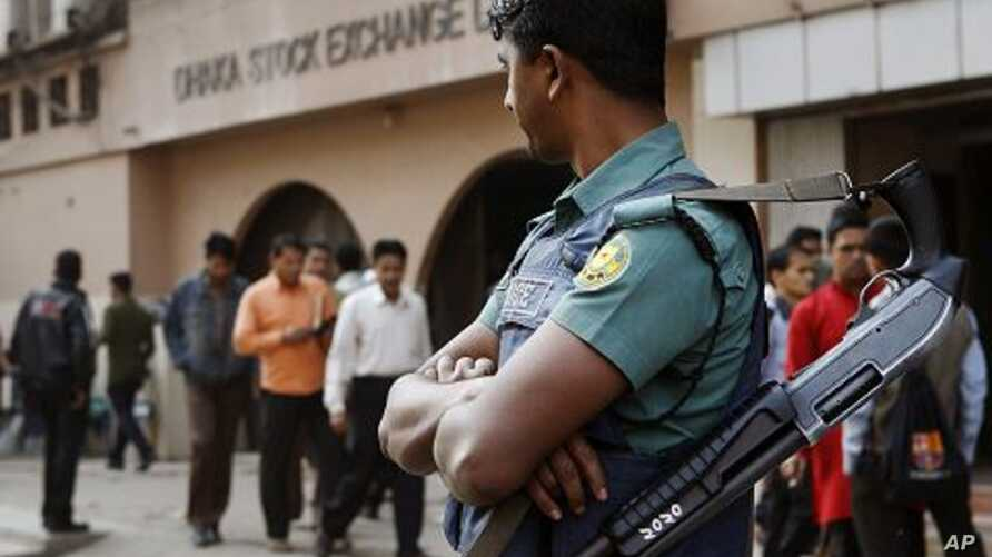 A Bangladeshi riot policeman stands guard in front of the Dhaka Stock Exchange during a demonstration in Dhaka, Bangladesh, January 24, 2012.